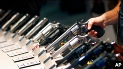 FILE - Handguns are shown at the Smith & Wesson booth at a trade show in Las Vegas, Jan. 19, 2016. Mexico has sued U.S. gun companies and distributors, arguing that their commercial practices have unleashed tremendous bloodshed in Mexico.