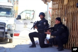FILE - Tunisian police officers take positions as they search for attackers still at large in the outskirts of Ben Guerdane, southern Tunisia, March 8, 2016.