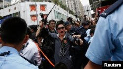 A plainclothes policeman wields a baton during a confrontation between protesters demonstrating against mainland traders and local residents, at Yuen Long district near the border with mainland China, in Hong Kong, March 1, 2015.