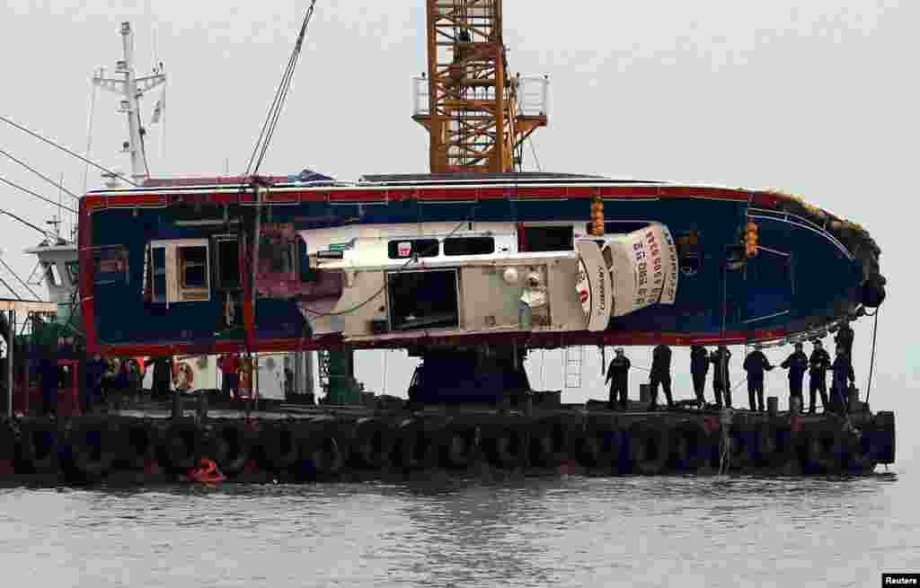 A capsized fishing boat is lifted during its salvation operation in the sea off Incheon, South Korea.