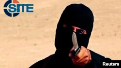 FILE - A masked, black-clad militant, who has been identified by the Washington Post newspaper as a Briton named Mohammed Emwazi, brandishes a knife in this still image from a 2014 video obtained from SITE Intel Group.
