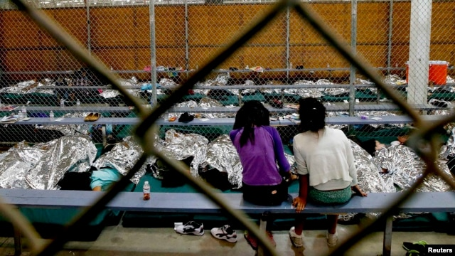 Two young girls watch a World Cup soccer match on a television from their holding area at a detention facility in Nogales, Arizona.