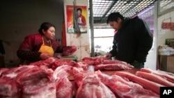 在上海,一位顾客在肉铺挑肉(资料照片)