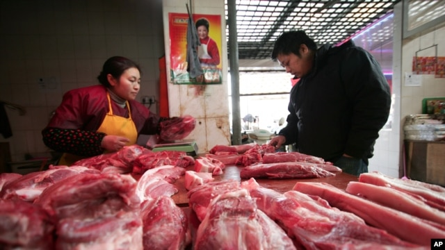 FILE - A customer looks at meat at a shop in Shanghai.