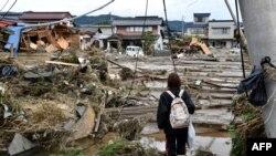 Seorang wanita melihat rumah-rumah yang rusak akibat banjir di Nagano pada 15 Oktober 2019, setelah Topan Hagibis melanda Jepang pada 12 Oktober 2019. (Foto: AFP)