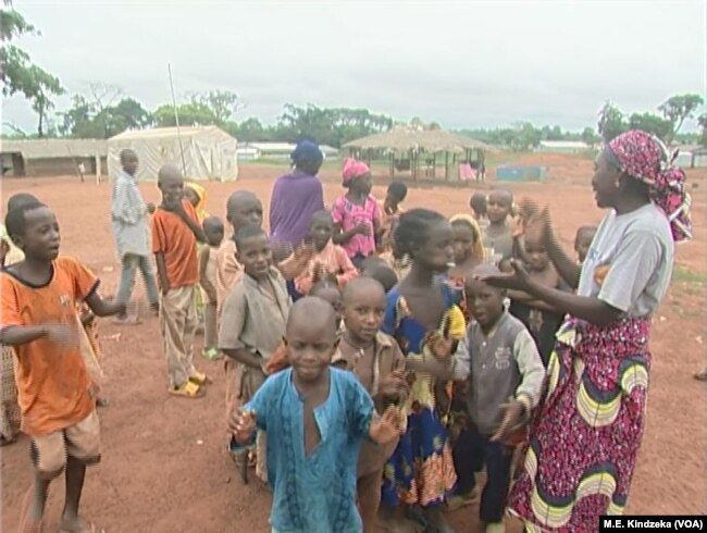 CAR refugee children at Garoua Boulaye play with a host parent.