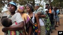 Des femmes, certaines avec leur bébé, s'alignent pour voter à Luanda, Angola, 31 août 2012.