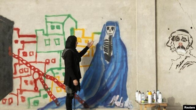 Afghan artist Malina Suliman paints graffiti on a wall in Kandahar city December 30, 2012.