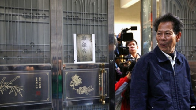 File Photo shows Lin Zuluan, a representative from the village of Wukan in Lufeng county, Guangdong province, followed by members of the international media as he leaves his home, December 21, 2011