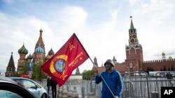 Seorang pria berpose dengan bendera merah di depan Lapangan Merah dalam peringatan 75 tahun kekalahan Nazi dalam Perang Dunia Kedua di Moskow, Rusia, 9 Mei 2020.