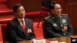 FILE- Xu Caihou, vice chairman of the CPC Central Military Commission, right, and Chongqing party secretary Bo Xilai attend the closing session of the National People's Congress in Beijing's Great Hall of the People in China, March 14, 2012.