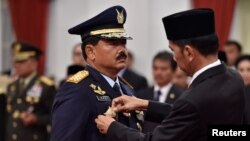Indonesian President Joko Widodo attaches the rank to the new Armed Forces Chief Marshall Hadi Tjahjanto during an inauguration ceremony at the Presidential Palace in Jakarta, Indonesia, Dec. 8, 2017, in this photo taken by Antara Foto.