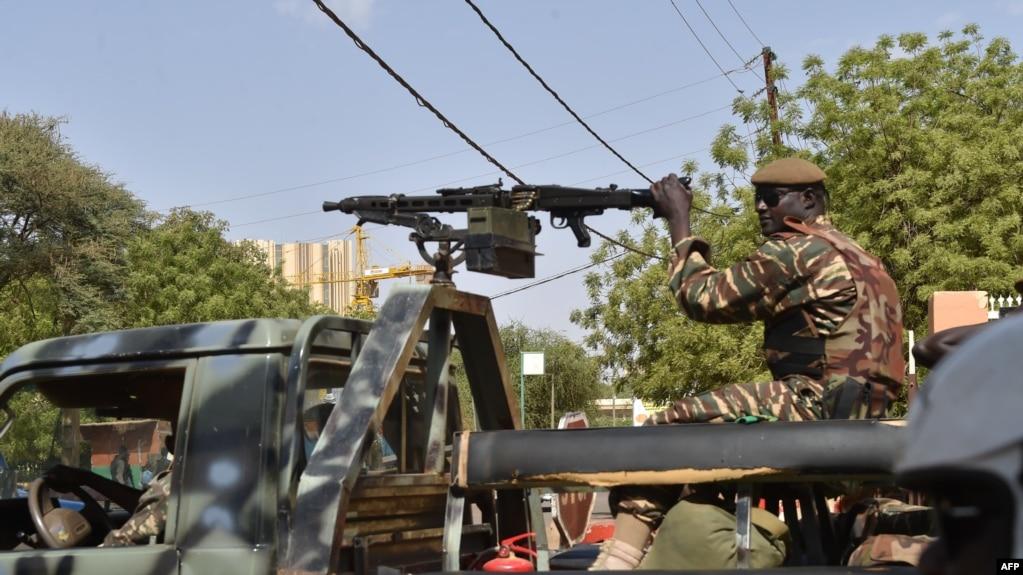 Des soldats patrouillent à bord de leur camion militaire à l'entrée d'un bureau de vote à la mairie de Niamey lors du second tour de l'élection présidentielle, le 20 mars 2016.
