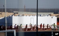 Migrant teens walk in a line through the Tornillo detention camp in Tornillo, Texas, Thursday, Dec. 13, 2018. The Trump administration announced in June 2018 that it would open the temporary shelter for up to 360 migrant children in this isolated corner of the Texas desert. Six months later, the facility has expanded into a detention camp holding thousands of teenagers.