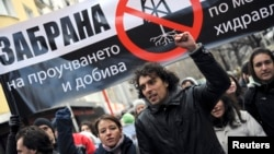"""FILE - Protesters shout slogans and carry a banner that reads """"Ban shale gas tests through hydraulic fracturing"""" during a rally in central Sofia, January 14, 2012."""