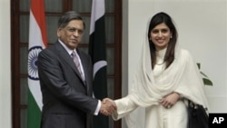 Indian Foreign Minister S.M. Krishna, left and his Pakistan counterpart Hina Rabbani Khar pose for photographs before their talks in New Delhi, India, Wednesday, July 27, 2011. The ministers met Wednesday for the first time since the nuclear-armed rivals