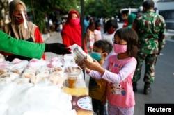 Anak-anak mengenakan masker menerima bantuan makanan gratis di tengah pandemi virus corona di Jakarta. (foto: ilustrasi)