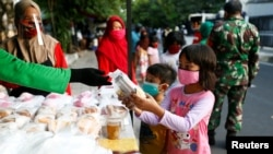 Anak-anak mengenakan masker menerima bantuan makanan gratis di tengah pandemi virus corona (Covid-19) di Jakarta, 14 Mei 2020. (Foto: Reuters)