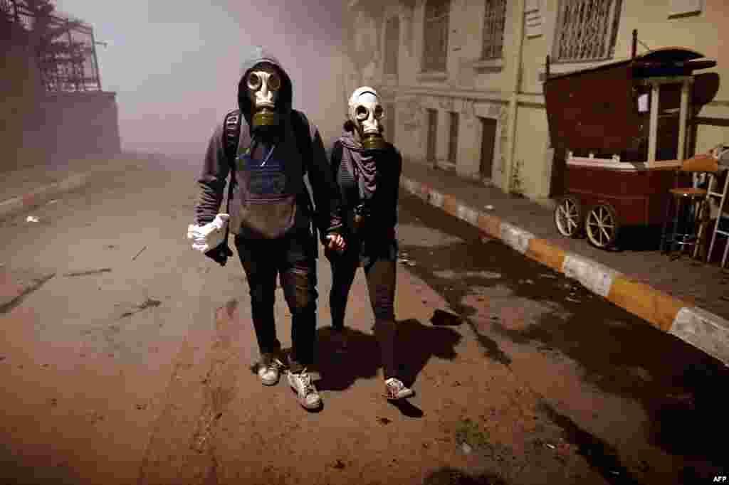 دو شهروند ترکیه با ماسک بر صورت در خیابانی نزدیک به میدان تقسیم استانبول، در جریان تظاهرات