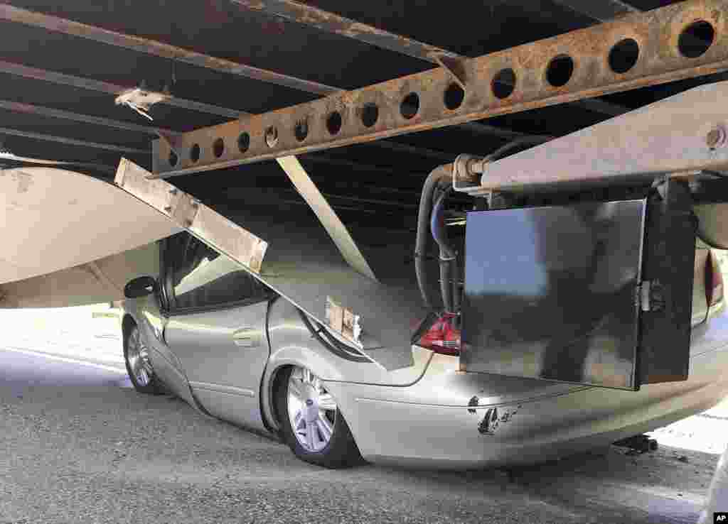 In this photo released by the Uxbridge Fire Department on its Facebook page, a car sits wedged under a tractor-trailer on Route 146 in Uxbridge, Massachusetts. The motorist, whose name wasn't made public, climbed out of the driver's side door of the crushed car and wasn't seriously hurt.
