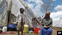 一名流离失所的妇女和男孩在肯尼亚的临时住所前(2008年4月资料照)