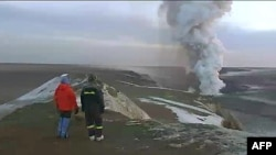 In this image from television, people watch a plume rising from the Grimsvotn volcano in Iceland, May 25 2011