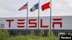 Flags fly over the Tesla Gigafactory 2, which is also known as RiverBend, a joint venture with Panasonic to produce solar panels and roof tiles in Buffalo, New York, Aug. 2, 2018.