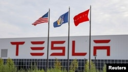 Flags fly over the Tesla Inc. Gigafactory 2, which is also known as RiverBend, a joint venture with Panasonic to produce solar panels and roof tiles in Buffalo, New York, U.S., Aug. 2, 2018.