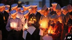 FILE - Maine Maritime Academy students in Castine, Maine, bow their heads Oct. 6, 2015, during a vigil of hope for the missing crew members of El Faro. All 33 members of the crew were killed.