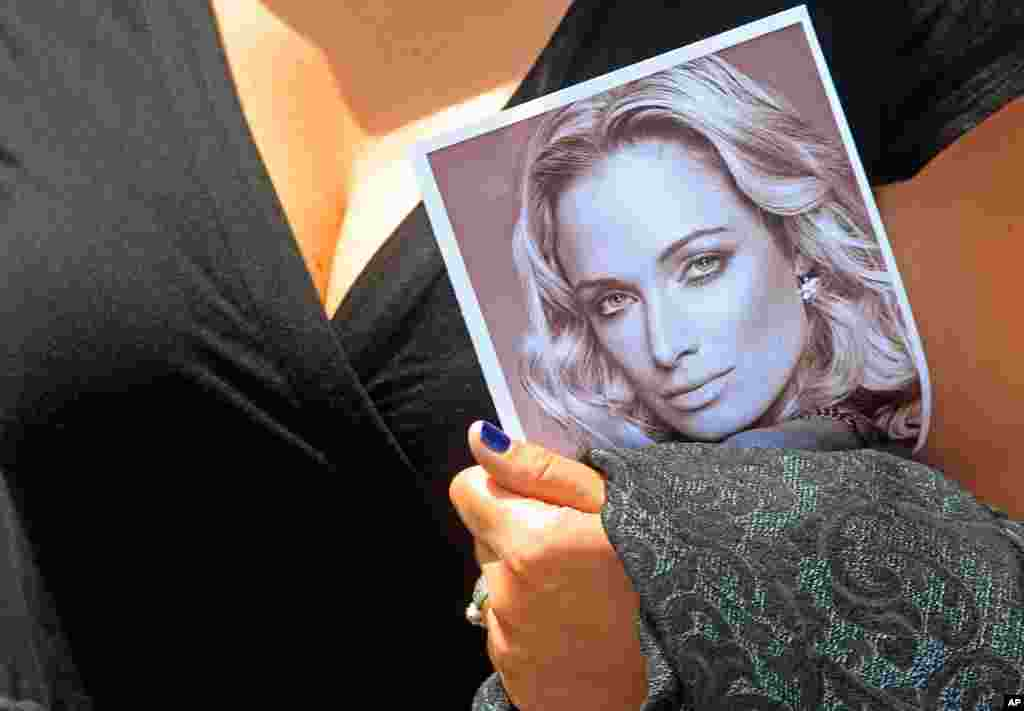 A woman holds a photo of Reeva Steenkamp as she leaves her funeral in Port Elizabeth, South Africa, February 19, 2013.