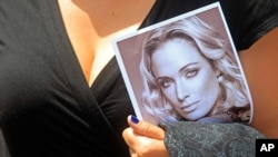 A woman holds a photo of Reeva Steenkamp as she leaves her funeral in South Africa, February 19, 2013.