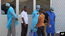 Medical personnel at emergency entrance of hospital receive suspected Ebola virus patients, Conakry, Guinea, March 29, 2014.