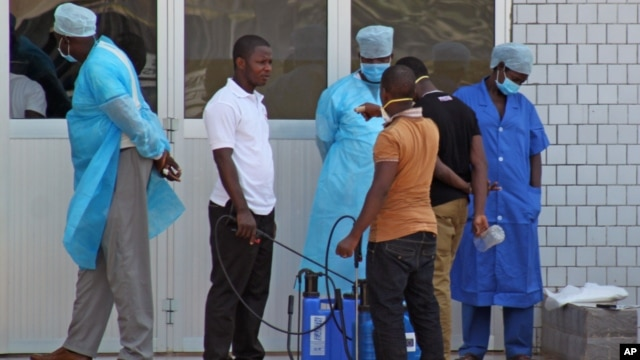 In this photo taken on March 29, 2014, medical personnel at the emergency entrance of a hospital receive suspected Ebola virus patients in Conakry, Guinea.