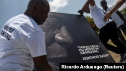 """People place a portrait of late Haitian President Jovenel Moise with a quote from him that reads in creole """"I try, you don't give up. Continue fighting"""" at a memorial outside the Presidential Palace, a week after his assassination, in Port-au-Prince, Haiti July 14, 2021."""