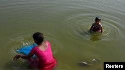 ARCHIVO - Una mujer lava ropa mientras su hija se baña en el río Yamuna durante un día caluroso en Delhi, India, el 24 de abril de 2017.