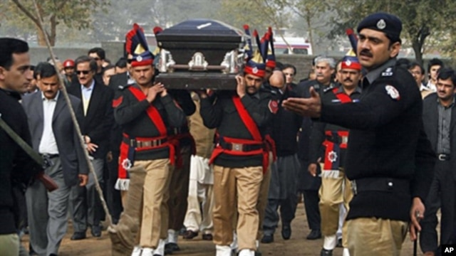 Pakistani police guards carry the coffin of late Punjab governor Salman Taseer during the funeral procession in Lahore on Jan 5, 2011.
