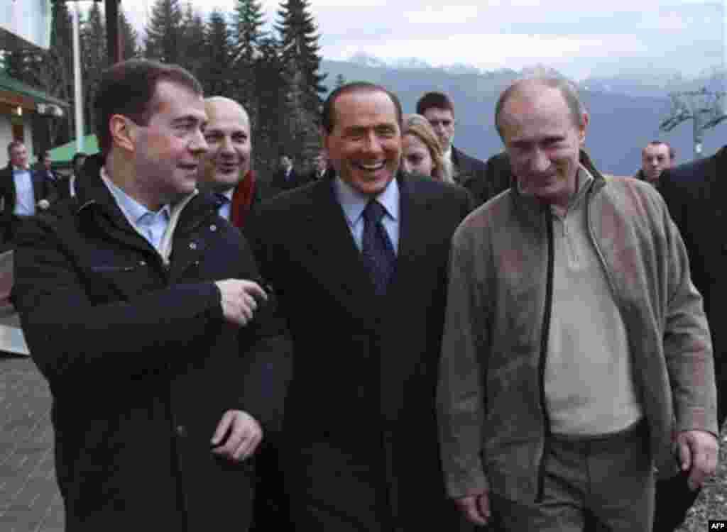 Russian President Dmitry Medvedev, left, Prime Minister Vladimir Putin, right, and Italian Prime Minister Silvio Berlusconi walk in the mountain resort of Krasnaya Polyana near the Black Sea resort of Sochi, southern Russia, Friday, Dec. 3, 2010. Ita