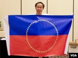 陈维明在会场展示他设计的未来中国旗帜(美国之音包小祥拍摄)