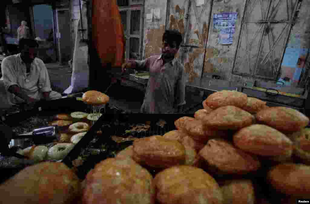 """Para penjual menyiapkan """"khajla"""", jajanan lokal yang biasa dikonsumsi sebagai hidangan berbuka puasa (Ta'jil) pada bulan Ramadan, di Karachi, Pakistan."""