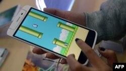 """Một nhân viên trong cửa hàng bán điện thoại ở Hà Nội chơi trò chơi Flappy Bird. Hơn một nửa dân số Việt Nam truy cập vào Internet và có nhiều tài năng công nghệ, trong đó có """"hiện tượng"""" trò chơi Flappy Bird hồi năm 2014."""