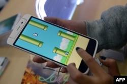 河内一家智能手机店的雇员在玩Flappy Bird(像素鸟)游戏。