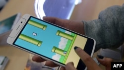 An employee plays the game Flappy Bird at a smartphone store in Hanoi, Feb. 10, 2014.