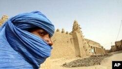 ေရၾကည္ရာ ျမက္ႏုရာ လွည့္လည္ေနထိုင္ေသာ Tuareg လူမ်ိဳး တစ္ဦးအား မာလီႏိုင္ငံ၊ Timbuktu ျမိဳ ႔ရွိ ၁၃ ရာစု ဗလီ အနီးတြင္ ေတြ႔ရပံု