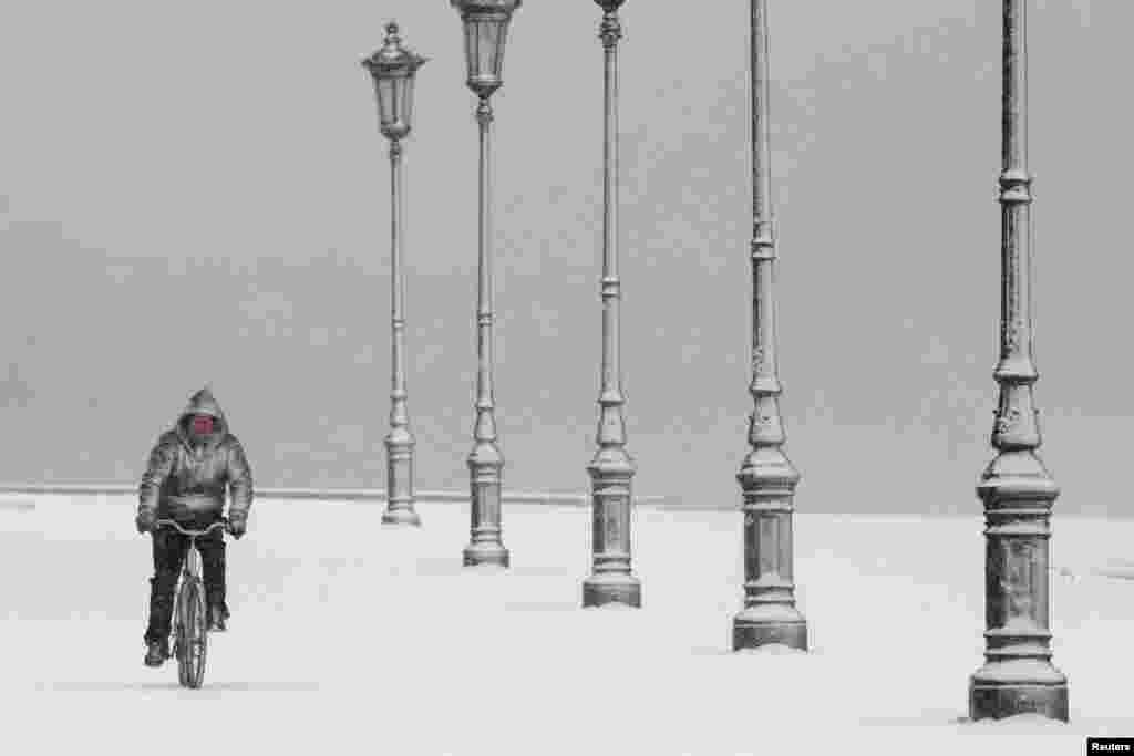 A man rides his bike during heavy snowfall at the seaside promenade of the northern port city of Thessaloniki, Greece.