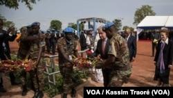 Le secrétaire général de l'ONU, Antonio Guterres, au milieu de deux casques bleus, déposent une gerbe de fleurs en mémoire des soldats onusiens décédés au Mali, 30 mai 2018. (VOA/Kassim Traoré)
