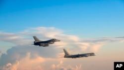 台灣國防部公佈的資料照顯示一架台灣戰機(左)在一架中國轟炸機附近飛行(2018年5月25日)