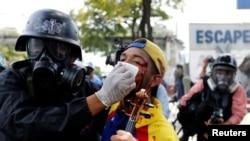 Seorang demonstran yang luka-luka dibantu oleh petuas keamanan saat protes menentang pemerintahan Presiden Venezuela Nicolas Maduro di Caracas, Venezuela, 22 Juli 2017.