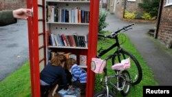 Bilik telepon umum warna merah di Inggris yang berubah fungsi menjadi perpustakaan di Marton cum Grafton, Inggris utara.