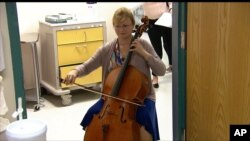 FILE - In this image taken from video, cellist Martha Vance plays for a patient at Medstar Georgetown University Hospital in Washington, Oct. 11, 2017.