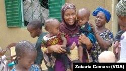 Madame Fadiga de l'Association des Mamans d'Enfants Hydrocéphales de Guinée, entourée d'enfants dans un centre d'hébergement près de Conakry (VOA/Zakaria Camara)